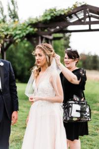 makeup artist touches up brides veil